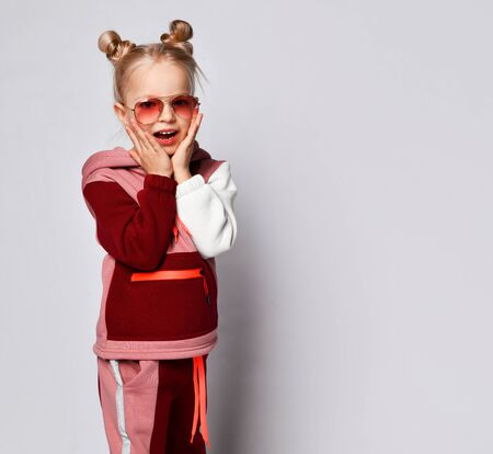 Worried or frightened little girl in stylish jogging suit and sunglasses touching chicks with hands. Stylish and sporty kids, emotions, childhood. Studio portrait isolated on light grey, copy space