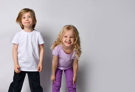 Little blonde girl in purple t-shirt and pants and boy in black and white casual clothes. They smiling, posing isolated on white background. Childhood, fashion, advertising. Close up, copy space