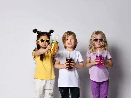 Little boy and girls in sunglasses, colorful casual clothes. They holding cocktail bottles and smiling while posing isolated on white studio background. Childhood, fashion. Close up, copy space