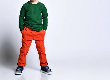 Cropped photo of a boy in a green jumper, orange pants, blue sneakers. He put his hands in his pockets, posing isolated on a white background. Childhood, fashion, advertising. Full length, copy space