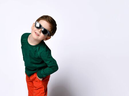 Little child in sunglasses, green jumper and orange pants. He is smiling while posing isolated on white studio background. Childhood, fashion, advertising. Close up, copy space Zdjęcie Seryjne