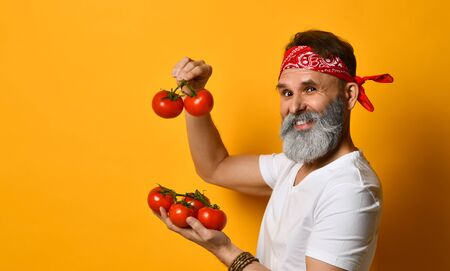 Gray-bearded, middle-aged guy in red bandana, white t-shirt and bracelet. He is smiling, showing red tomatoes on twigs, posing standing sideways on orange background.