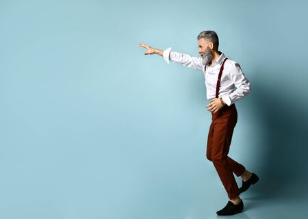 Gray-haired, bearded man in white shirt, brown pants and suspenders, black loafers. He runs looking back, raised his hand up, posing on blue background. Fashion and style.