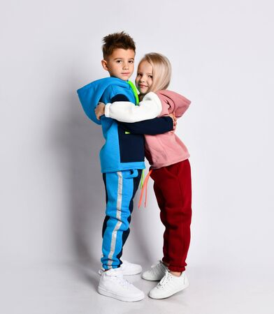Little kids, brother and sister, in hoods, colorful tracksuits and sneakers. Elder brother hugging his younger sister. , posing sideways isolated on white. Childhood, fashion, advertising and sport. Stock Photo