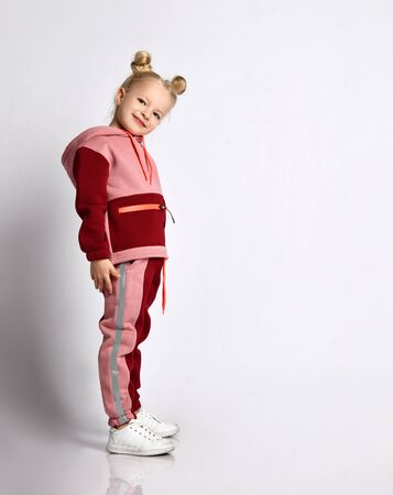 Cute blonde model with buns hairstyle, in colorful tracksuit, sneakers. She smiling, performing exercises, posing sideways isolated on white. Childhood, fashion and sport. Full length, copy space