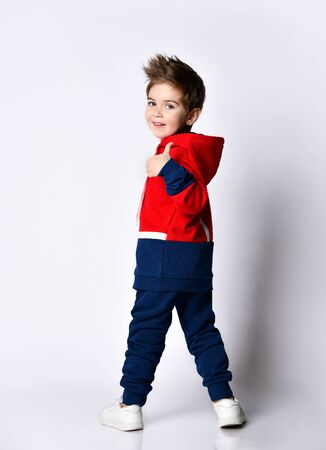 Little blond boy in blue and red tracksuit, sneakers, sunglasses. Smiling turning back, showing thumb up, posing isolated on white. Childhood, fashion, advertising, sport. Full length, copy space