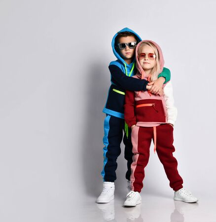 Elder brother hugging his younger sister. Stylish sporty kids in colourful tracksuits and sunglasses. Childhood, togetherness, friendship, loving siblings. Full length portrait isolated on light grey