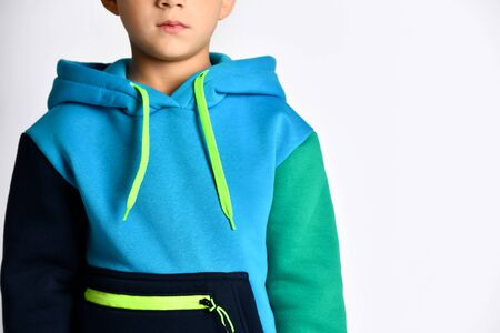 Fashionable little boy in black, blue and navy sports jacket standing straight and concentrated. Stylish and sporty kids, healthy leisure, childhood. Close up view isolated on light grey, copy space