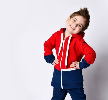 Little blond boy in blue and red tracksuit. He is smiling, put hands on hips, posing isolated on white studio background. Childhood, fashion, advertising and sport concept. Close up, copy space