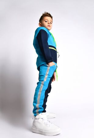 Side view shot of a little schoolboy in a bright cotton tracksuit standing with hands in pockets looking down. Children fashion, young athletes, stylish. Full length portrait isolated on light gray.