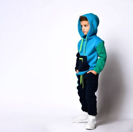 Side view shot of little schoolboy in bright cotton tracksuit standing with hands in pockets looking down. Children fashion, young athletes, being stylish. Full length portrait isolated