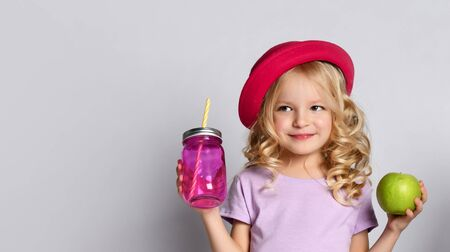 Little blonde kid in red hat and purple blouse. She smiling, holding pink cocktail bottle and green apple, posing isolated on white background. Childhood, healthy nutrition. Close up, copy space Imagens