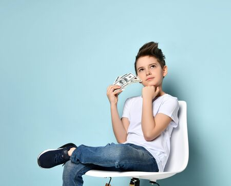 Concentrated boy sits on chair holding dollars and touching chin with hand thinking how to earn more. Big salary, successfull business, crisis is not scary. Portrait isolated on light blue Reklamní fotografie
