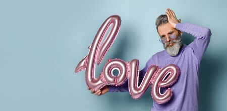 Gray-haired, bearded, mature male in sunglasses, purple sweater. Holding pink balloon in form of word love, straightens his hair, posing on blue background. Fashion and style. Close up, copy space