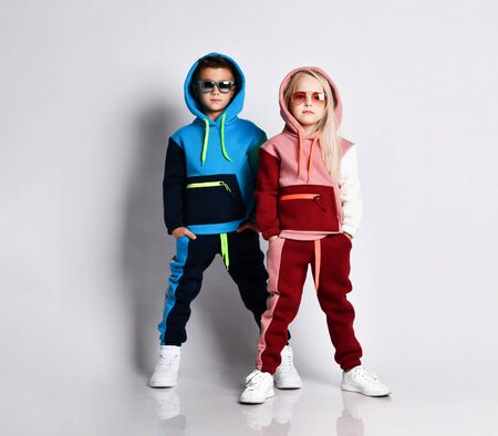 Little kids, boy and girl, in sunglasses and hoods, colorful tracksuits, sneakers. They posing isolated on white studio background. Childhood, fashion, advertising and sport.