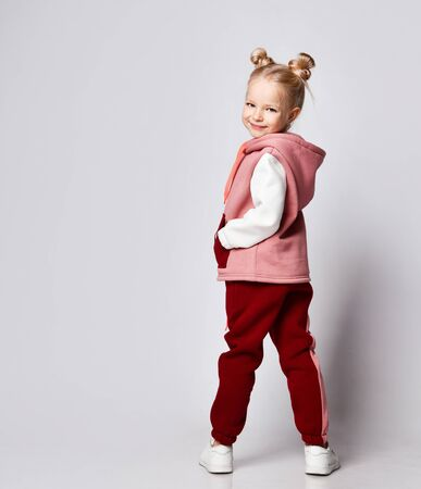 Cute blonde model with a haircut in the form of buns, in a multi-colored tracksuit, sneakers. She smiles, stands with her back half a turn, isolated on white. Childhood, fashion and sport.