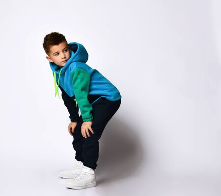 Stylish little boy in a warm tracksuit rests his hands on his knees and looks away.