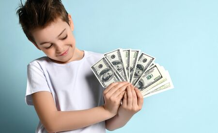 Stylish smiling kid looking on fan of dollar banknotes in his hands with admire imagining how much he can purchase. Emotions, luck, wealth, jackpot, millionaire. Half-length portrait isolated on blue