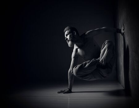 gray-haired bearded male yogi with a naked torso in his pants practices yoga. Legs in lotus position with one hand resting on the wall and the other on the floor.  Black and white photo Stock Photo