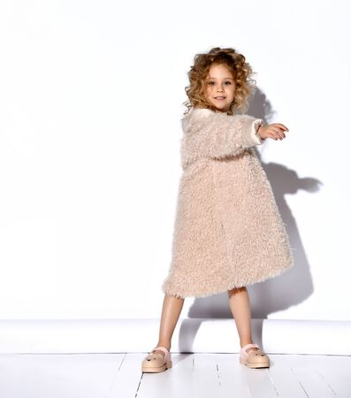 Little blond curly model in a gold necklace, fluffy beige dress and a fur coat, shoes. She spread her hands, fooling around, posing on a white background photo. Childhood, fashion. Full length, copy space
