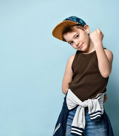 teenage child in a cap, brown t-shirt, jeans and a sweatshirt is tied at the waist. He smiles and shows strength in his hand, posing against a blue studio background. Adolescence, fashion.