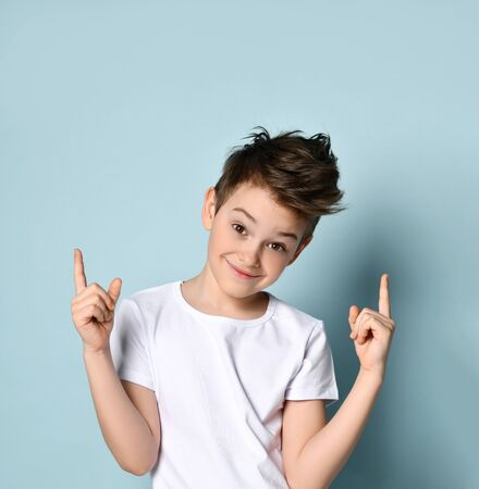 Naughty kid looking at camera with broad sly smile pointing his index fingers up getting up to joke or mischief. Facial expression, emotions, childhood. Half-length portrait isolated on light blue
