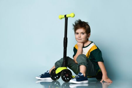 Stunning boy in a bright T-shirt, gray jeans and sneakers. He rolled and sat down to rest, posing on a scooter on a blue studio background.