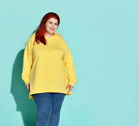 Plump red-haired woman in stylish casual attire posing calmly with beautiful smile. Self esteem, diet, love yourself, charming plus-size, body positive. Three quarter length portrait isolated on blue