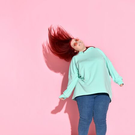 Joyful young fatty woman in glasses with flowing red hair smiling and jumping on place. Stylish, trendy, chubby lady, motivation, diet, self-acceptance. Three quarter length portrait isolated on pink