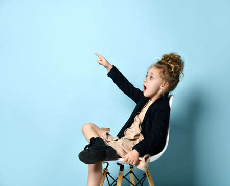 Nice little girl with lifted up golden hair in black blazer and beige dress sits cross-legged in office chair, pointing aside and giving orders, isolated on blue. Office style, little businesswoman Imagens