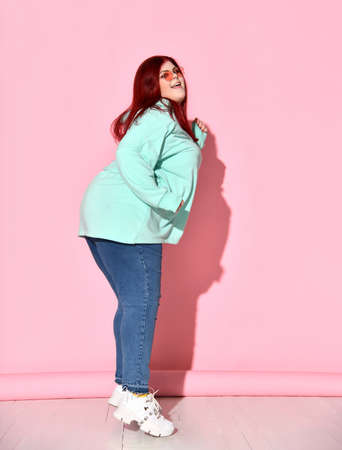 Side shot of a happy curvy female in stylish and cosy clothing standing on her toes in process of jumping up on place, isolated on pink. Active lifestyle, love yourself, ample girl, be you, dieting.
