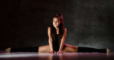 Young smiling girl gymnast in black sport body and special footwear sitting in twine over dark background. Rhytmhic gimnastics beauty cocnept Stock fotó