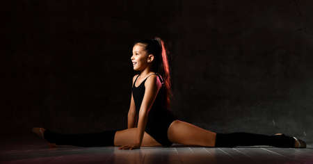 smiling girl gymnast in black sport body and special shoes sitting in a twine face forward over a dark background. Rhythmic Gymnastics Beauty Concept Stock fotó