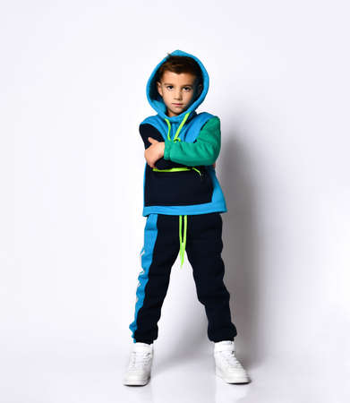 Little brunette child in colorful sport suit and sneakers. He has put his hood on while posing isolated on white studio background. Childhood, fashion, advertising. Full length, copy space