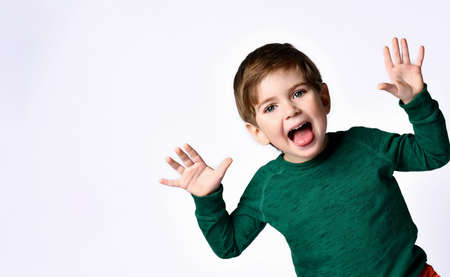 Cute brunette kid dressed in green jumper. He raised his hands up, opened mouth and looking overjoyed, posing isolated on white background. Childhood, fashion, advertising. Close up, copy space Banco de Imagens - 150647864