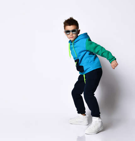 Little kid in sunglasses, colorful tracksuit and sneakers. He is posing in a jump, isolated on a white background. Childhood, fashion, advertising. Full length, copy space. Stock Photo