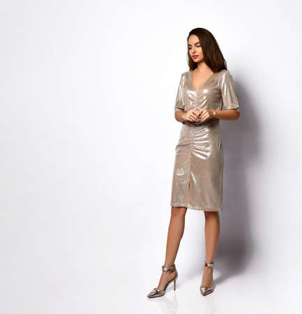 Elegant young woman with slim long legs posing calmly in short silver sequin dress and high heels. Glamour, stylish clothing, fashion for women. Full length portrait isolated on white. Copy space