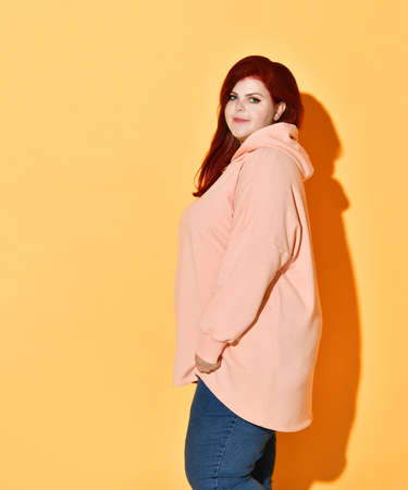 Charming model of large sizes posing in stylish casual clothes, looking over her shoulder, isolated on orange. Stylish and fashionable, chubby lady, motivation, diet, self-acceptance