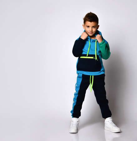 boy in stylish cotton jym suit standing with legs apart keeping hands in pockets. Children athletes, active lifestyle, fashion sportswear design. Full length portrait isolated on light grey Stock Photo
