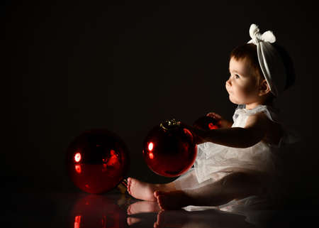 Little girl in a white headband and barefoot dress. She holds two red balls, Christmas decorations, sitting on the floor. Twilight, black background. New year, holidays. Close, copy space, side view.