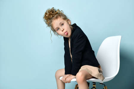 Naughty little girl dressed in business style wearing her blond curly hair up sitting in office chair leaning forward and lolling out, isolated on blue. Little businesswoman, snappy dresser, childhood