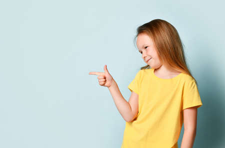 Cute blonde little female in yellow t-shirt. She is smiling and pointing to the side by forefinger while posing against turquoise studio background. Childhood, gestures, emotions. Close up, copy space