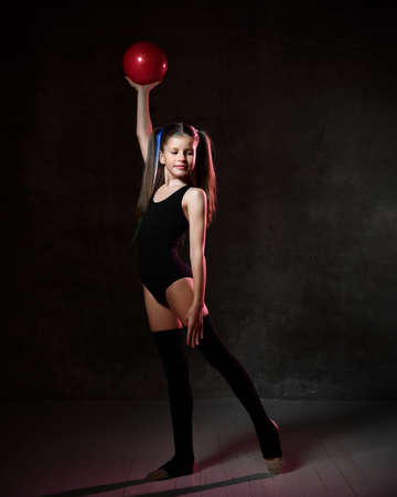 Young smiling girl gymnast with long hair in black sport body and uppers standing and holding pink gymnastic ball in raised hand over dark background. Rhytmhic gimnastics beauty cocnept Stock fotó - 150647929