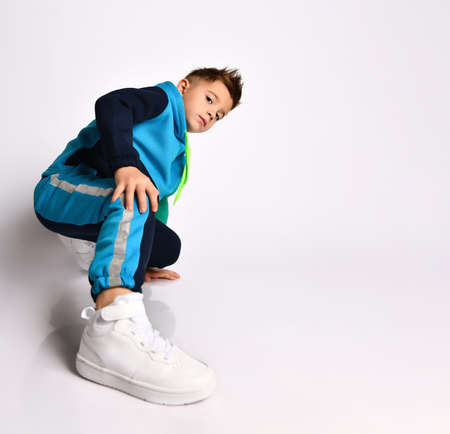 Little son in colorful tracksuit, sneakers. He performing exercises or kick by his leg, posing isolated on white background. Childhood, fashion, advertising and sport. Full length, copy space Stock Photo