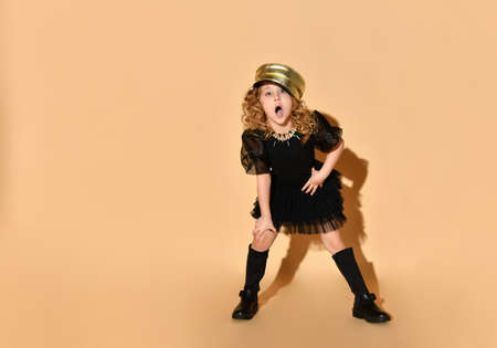 Pretty little girl in black dress, golden cap on curly hair and black boots sings song leaning forward with hand on knee. Childhood, trendy kid, glamour. Full length shot isolated on peach background Stock Photo