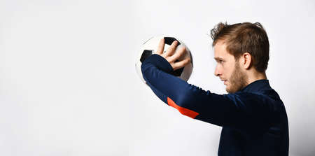 Blond man, professional soccer player in blue tracksuit is going to throw a ball, posing sideways isolated on white studio background. Concept of sport, balance and agility. Close up, copy space