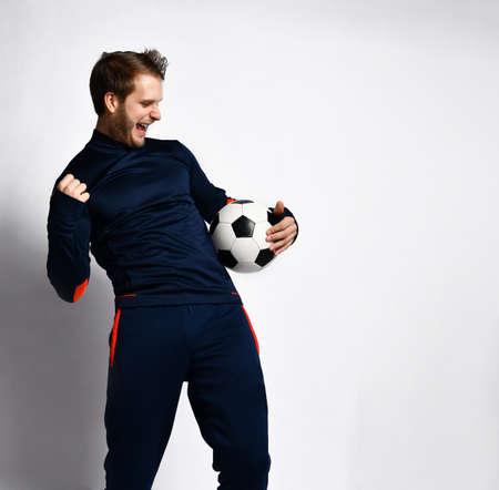 Blond guy, professional soccer player in blue tracksuit is looking overjoyed and holding a ball, posing isolated on white studio background. Concept of sport, balance and agility. Close up, copy space