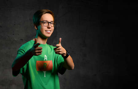 Young smiling teen boy in green t-shirt, jeans and glasses standing and showing good thumbs sign over dark background. Stylish casual clothing for teenagers, expressing emotions concept