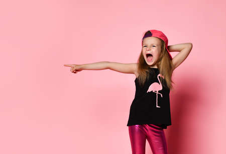 Little blonde child in cap, black blouse with printed flamingo and leggings. She screaming and pointing to the side by forefinger while posing against pink studio background. Close up, copy space