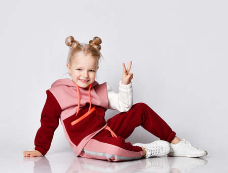 Charming little girl in beautiful fashionable sportsuit sitting on floor showing two fingers in victory sign. Stylish and sporty kids, happy childhood. Close up portrait isolated on light grey